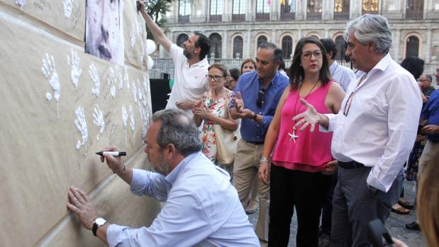 Jesús Labrador firma en el mural instalado en la plaza del Ayuntamiento./ Ana Pérez.